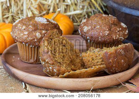 Closeup of a sliced pumpkin muffin on a wooden plate