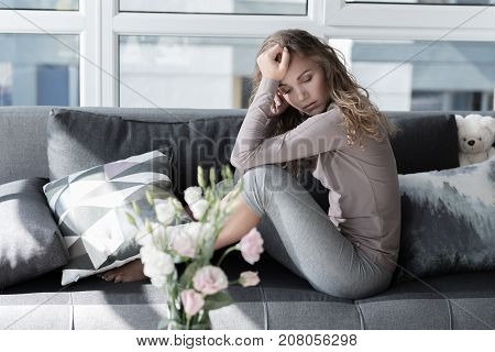 Full length portrait of sorrowful young woman sitting on comfortable sofa in living room. Sorrow concept