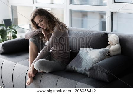 Portrait of mirthless lady sitting on comfortable sofa in living room. Sorrow concept