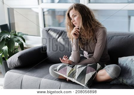 Full length side view sorrowful female sitting on cozy sofa in living room. Melancholy concept