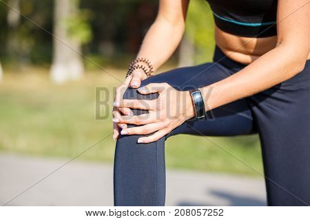 Female runner holding aching knee at morning jogging. Sport injury concept background