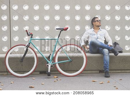 Urban Man Sitting On A Bench Outdoors With Worried Expression