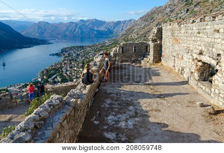 KOTOR MONTENEGRO - SEPTEMBER 8 2017: Unknown tourists visit ruins of fortress of St. John (Illyrian fort) over city of Kotor and Bay of Kotor Montenegro