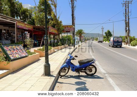 RHODES, GREECE - AUGUST 2017: Blue scooter bike is staying parked near traditional Greek tavern on Rhodes island