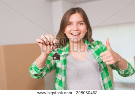 Happy apartment owner or renter showing keys and making thumbs up gesture.