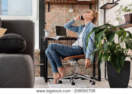 Hilarious girl is using phone for pleasant conversation and looking up with wide smile. She sitting near working place. Low angle. Copy space on left side