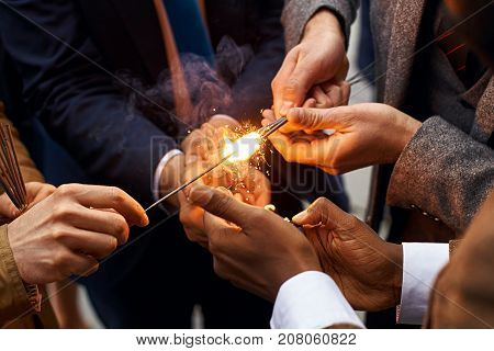 Hands of young people in suits holding burning sparkles fireworks