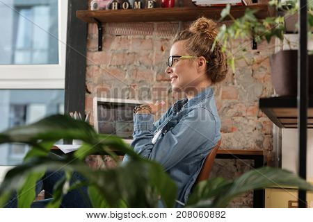 Cheerful girl is sitting near working place and looking ahead with kind smile. Profile. Copy space on left side