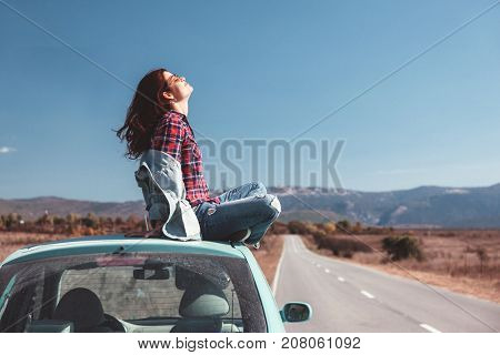 Hipster girl relaxing on the car roof in her autumn road trip, carefree and enjoying freedom and travel. Wanderlust concept scene.
