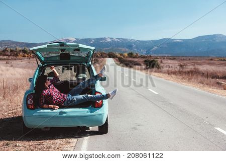 Hipster girl relaxing in the car trunk in her autumn road trip, carefree and enjoying freedom and travel. Wanderlust concept scene.
