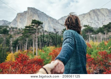 Back view of traveler man wearing sweater holding friend's arm in autumn woods and looking at mountain hill. Cold weather, fall colors. Wanderlust and follow me concept.