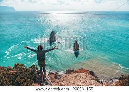 Back view of man traveler standing on mountain alone and looking at autumn sea landscape, arms up. Hiking in cold season. Wanderlust concept scene.