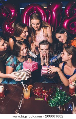 New Year party. Tired male at Christmas. Women attention with gifts for young man. Romantic mood at celebration, tiredness, too much gifts, spoiled child concept