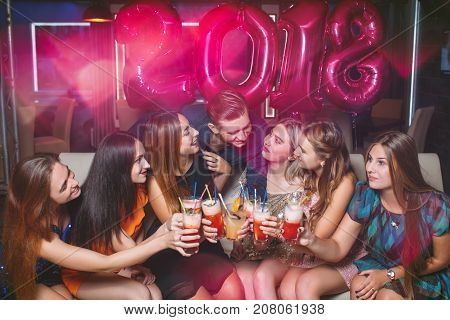 New Year 2018 celebration. Happy company. Christmas corporate party, friends in night club with cocktails, joyful toast. Pleasant leisure time, friendship concept