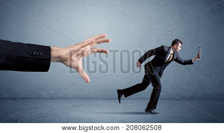 Young miniature businessman running from a big hand with blue background