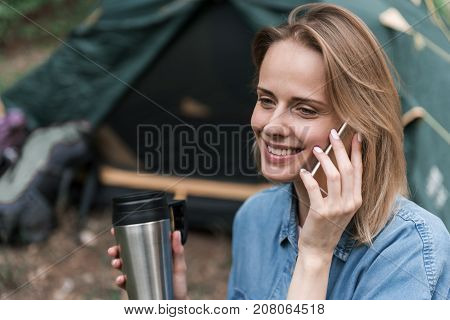 Portrait of happy young woman speaking by smartphone in camping. She is drinking hot beverage and smiling