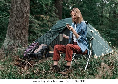Full length portrait of cheerful young woman typing message on smartphone while resting in the nature. She is sitting near tent and drinking hot beverage