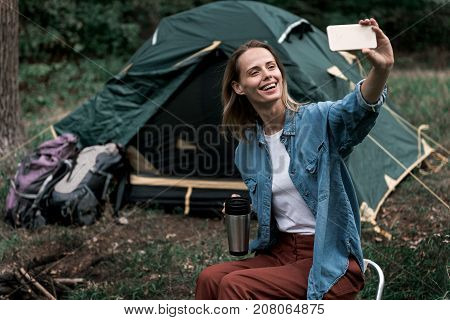 I must save this moment in memory. Portrait of happy female tourist making selfie on smartphone while sitting near tent in forest. She is drinking hot tea and laughing