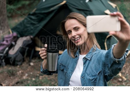 Spending wonderful day in the nature. Portrait of joyful young woman photographing herself on cellphone camera while drinking hot beverage. She is sitting in camping and smiling