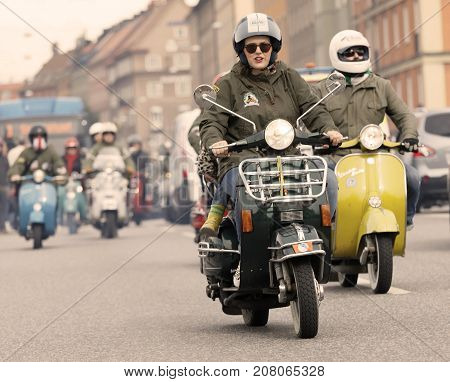 STOCKHOLM SWEDEN - SEPT 02 2017: Closeup of female mods and her child wearing old fashioned clothes driving beautiful old fashioned vespa scooter at the Mods vs Rockers event at the Saint Eriks bridge Stockholm Sweden September 02 2017