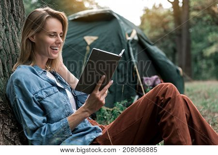 Portrait of excited female tourist is reading book with interest. She is leaning on tree in camping and laughing