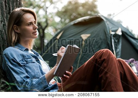 Pensive young girl is writing poem in her notebook with inspiration. She is sitting in forest and leaning back on tree. Tent on background