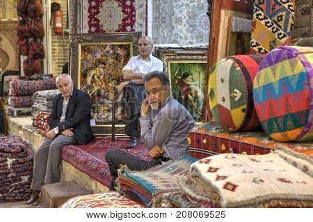 Fars Province Shiraz Iran - 19 april 2017: Three mature Iranian men are in the sales department of carpets inside the city bazaar.