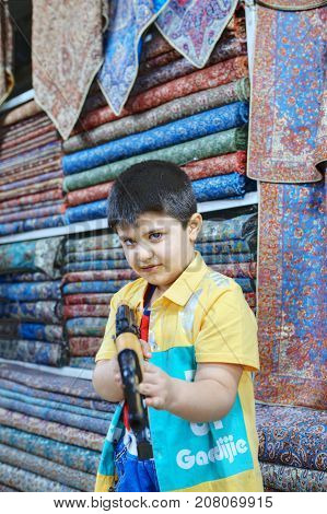 Fars Province Shiraz Iran - 19 april 2017: One unknown boy about 10 years old plays with a Kalashnikov toy automaton in the textile shop of the city bazaar.
