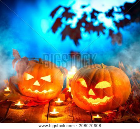 Halloween pumpkin head jack lantern with burning candles over wooden background. Halloween holidays art design, celebration. Carved Halloween Pumpkins with burning candles