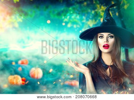 Halloween Witch pointing hand over dark magic field with  Pumpkins and magic lights in forest. Beautiful young surprised woman in witches hat and costume holding pumpkin. Wide Halloween party design