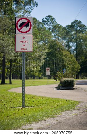 Traffic sign prohibiting the parking on the grass in the park. Nature. Road sign in the rest area. Rules for travelers.