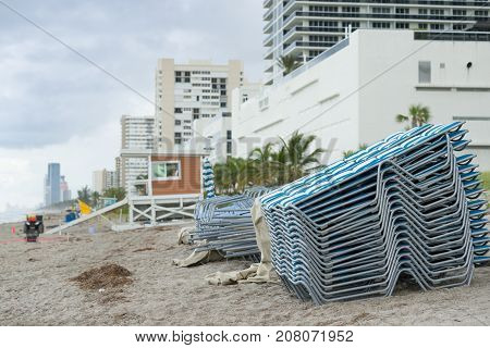 Stack of a sun loungers on the beach at early morning.
