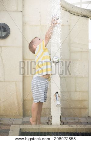 Cute little toddler boy washes the sand from his feet on white beach. Child playing with a beach shower.