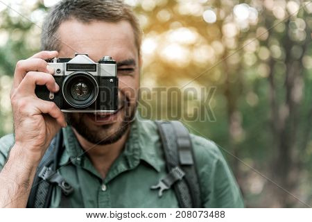Portrait of joyful male tourist taking photos in forest. He is standing with backpack and smiling. Focus on camera