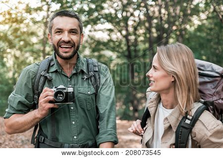 Portrait of excited beaded man taking photos of beautiful landscape in the woods. He is looking at camera and laughing. His wife is standing near him