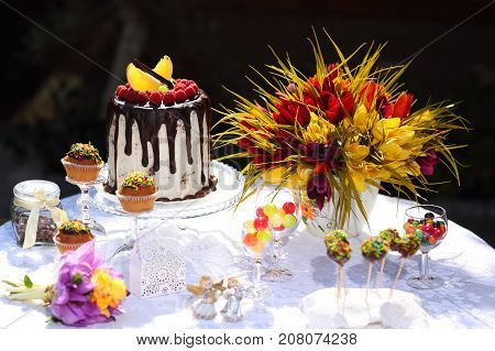 A festive table decorated with birthday cake with flowers and sweets. A table with a cake for the birthday of the child. Birthday party for children.