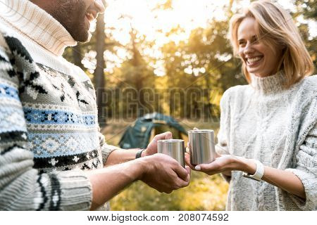 Excited young man and woman are drinking hot beverage together in the woods. They are looking at each other and laughing. Focus on cups in their hands