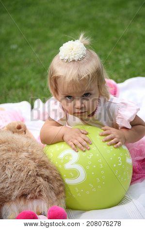 Adorable little girl lying on coverlet on grass. Little girl in the garden. Girl lying on coverlet - stock image
