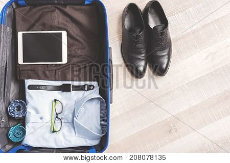 Shirt is near trousers in open suitcase. Shoes are near luggage at floor. Top view close up. Copy space on right side