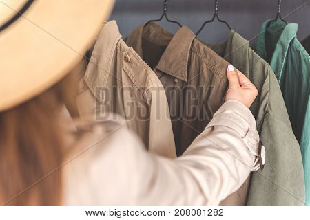 Woman is standing in wardrobe near hangers and choosing overcoat. Focus on hand taking cloth. Copy space on left side
