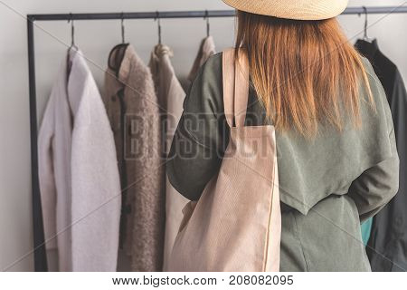 Girl wearing stylish overcoat is standing near hangers with other. She holding bag and turning back to camera. Copy space on left side