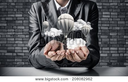 Closeup of business woman in suit presenting flying aerostate among clouds in her palms with dark brick wall on background. 3D rendering.