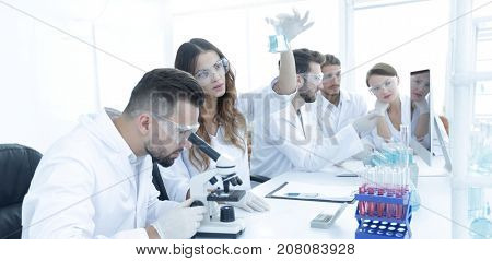 Scientists examining attentively pipette with blue fluid in laboratory
