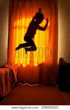 Sleepwalker boy jumps from bed in the moonlit window background blurred motion