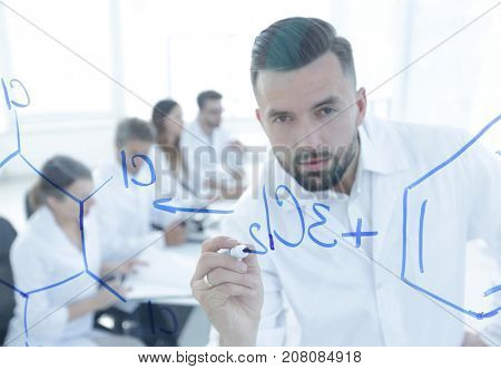 closeup of a serious scientist working with formulas