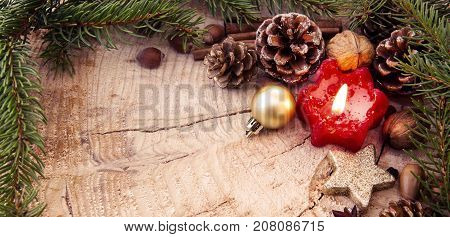 Christmas decoration with red Advent candle and fir branch frame, top view with copy space on wood.