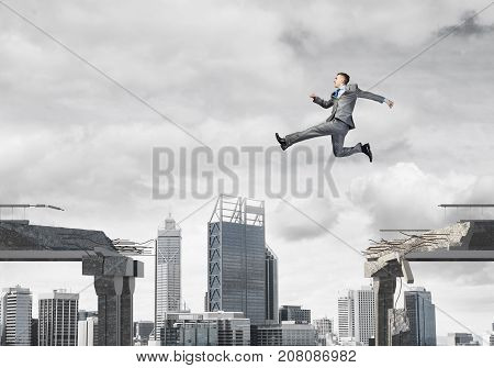 Businessman jumping over gap in concrete bridge as symbol of overcoming challenges. Dark sky and cityscape on background. 3D rendering.