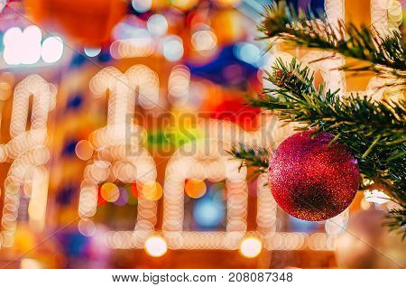 Bright Christmas and New Year background. Christmas and New Year decorations background. Red christmas shiny ball on fir branch.
