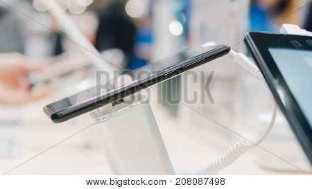 A New Smartphone On The Stand Of The Exhibition Close-up. New Models Of Gadgets At The Exhibition Of