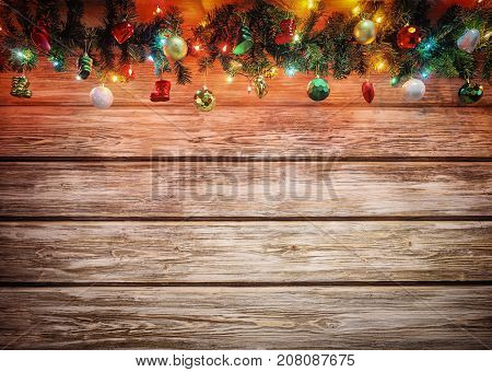 Christmas fir tree with decoration on wooden board. Bright Christmas and New Year background with empty space for text. Christmas decorations on wooden background